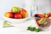Fresh tasty fruit salad on table, on light background — Stock Photo