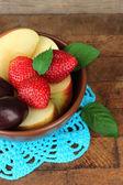 Fresh tasty fruit salad on wooden table — Stock Photo
