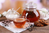 Teapot and cup of tea on table on light background — Stock Photo