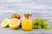 Glasses of juice with fresh fruits on grey wooden table — Stock Photo