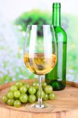 Tasty wine and ripe grape on green nature background — Stock Photo