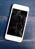 Moderní mobilní telefon s nefunkční obrazovka na dřevěné pozadí — Stock fotografie