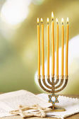 Menorah, star of David and page of Genesis book on wooden table, on bright background — Stock Photo