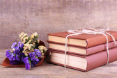Books and wildflowers on wooden table on wooden wall background — Stock Photo