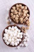 Brown and white refined sugar in color bowls on wooden background — Stock Photo