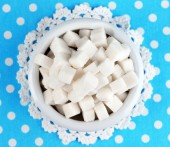 Refined sugar in color bowl on color fabric background — Stock Photo
