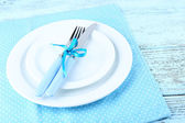 White plates, fork, knife and Christmas decoration on blue polka dot napkin on wooden background — Stock Photo