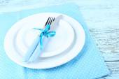 White plates, fork, knife and Christmas decoration on blue polka dot napkin on wooden background — Стоковое фото