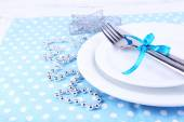 White plate, fork, knife and Christmas decoration on polka dot napkin on wooden background — Stock Photo