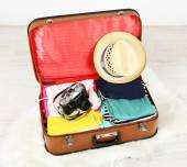 Female clothes and photo camera in old suitcase on light background — Stock Photo
