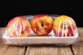 Peaches packed in food film on table on black background — Stock Photo