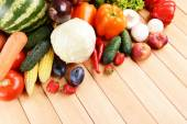 Fresh organic fruits and vegetables on wooden background — Stock Photo