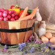 Big round basket with dried grass, vegetables, milk and fresh eggs on sacking background — Stock Photo #52913513