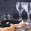 Slices of bread with butter and black caviar, glass jar of caviar and pair of small glasses on wooden table on dark background — Stock Photo #52916259