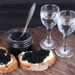 Slices of bread with butter and black caviar, glass jar of caviar and pair of small glasses on wooden table on dark background — Stock Photo #52916275