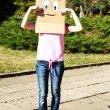 Woman with cardboard box on her head with sad face, outdoors — Stock Photo #52918777