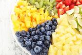 Skivad frukt på plattan på träbord — Stockfoto