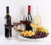 Bottles and glasses of wine, cheese and ripe grapes on table in room — Photo
