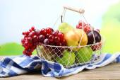 Assortment of juicy fruits in wicker basket on table, on bright background — Stock Photo