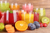 Glasses of tasty fresh juice, on wooden table. — Stock Photo