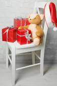 Christmas presents on white chair on brick wall background — Stock Photo