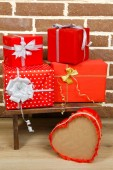 Christmas presents on stool on brown brick wall background — Stock Photo