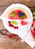 Fresh juicy watermelon slice  with cut out heart shape, filled fresh berries, on plate, on wooden background — Stock Photo