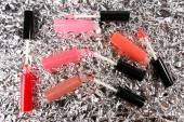 Beautiful lip glosses on foil background — Stock Photo