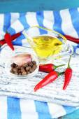 Set of spices and olive oil in glass sauce-boat, in cutting board, on color  wooden background — Stockfoto