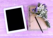 Tablet, notebook, pencil and bunch of field flowers on wooden background — Stock Photo