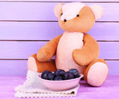 Toy bear and bowl of plums on napkin on wooden table on wooden wall background — Stock Photo