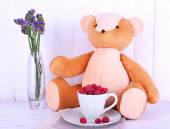 Toy bear and cup of raspberries on napkin on wooden wall background — Stock Photo
