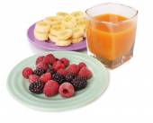 Slices of bananas with berries on plate with glass of juice isolated on white — Stock Photo