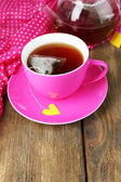 Cup of tea, teapot and tea bags on wooden table close-up — Stockfoto