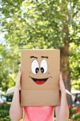 Woman with cardboard box on her head with happy face, outdoors — Stok fotoğraf