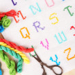 Handmade embroidered letters on white fabric and scissors on wooden background — Stock Photo #53024957