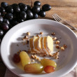 Tasty grape and cheese on plate, on wooden table — Stock Photo #53026393
