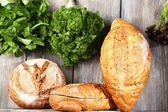 Fresh baked bread and fresh herbs, on wooden background — ストック写真