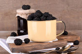 Sweet blackberries in color mug and tasty jam on  wooden background — ストック写真