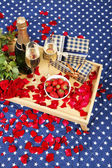 Romantic still life with champagne, strawberry and roses on bed — Stock Photo