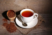 Cup of tasty rooibos tea, on wooden table — Stock Photo