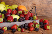 Ripe fruits and berries on tray wooden background — Foto Stock