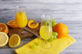 Glasses of juice with fresh fruits on grey wooden table — Foto Stock