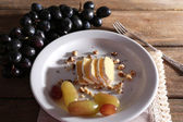 Tasty grape and cheese on plate, on wooden table — Stock Photo