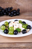 Tasty salad with grape and cheese on wooden table — Stock Photo