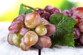 Bunch of ripe grape on wooden table on natural background — ストック写真