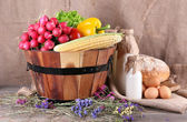 Big round wooden basket with vegetables, milk and bread on sacking background — Foto Stock