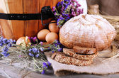 Big round wooden basket with vegetables, milk and bread on sacking background — Stock Photo