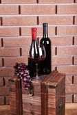 Bottle and glass of wine and ripe grape on box on brick wall background — Stock Photo