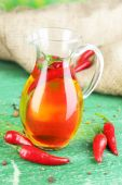 Homemade natural infused olive oil with red chili peppers on color wooden background — Stock Photo